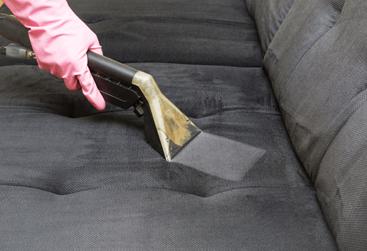 Image of a dirty sofa being cleaned by a upholstery cleaning hand tool.