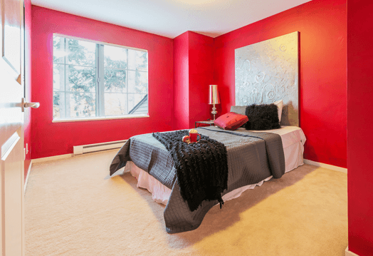 Image of a bedroom with a red painted wall.