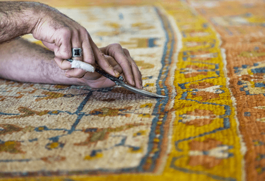 Image of a carpet cleaner trimming glints on the carpet using a scissor.