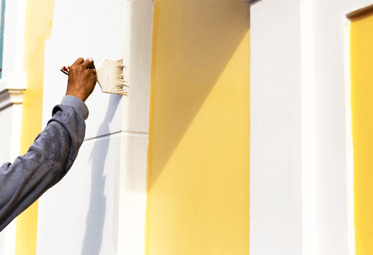 Image of a painter outside the house painting the wall.